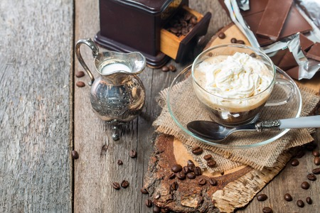 creamer: Glass cup of coffee with cream, chocolate and creamer on old wooden table Stock Photo
