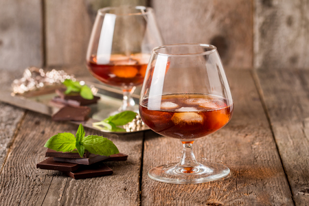 drunks: Vintage cognac still life with chocolate on wooden background