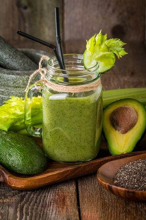 Healthy green juice smoothie with straw surrounded by avocado, cucumber,  celery and chia seeds on wooden background