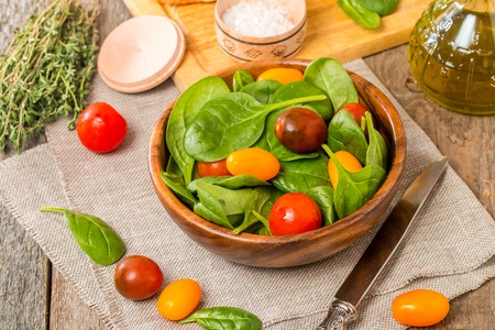 baby spinach: Salad made with baby spinach and cherry tomatoes in a wooden bowl with ingredients. Stock Photo