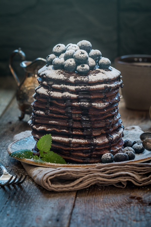Stack of Small chocolate Pancakes with chocolate syrup, powdered sugar and blueberries. healthy breakfast on old wooden background