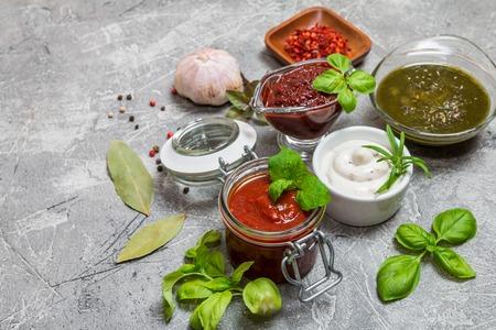 sauces: Various dip sauces on gray background, top view Stock Photo