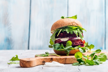 corn salad: Vegetarian burger made of beetroot, tomato, corn salad and arugula on wooden background
