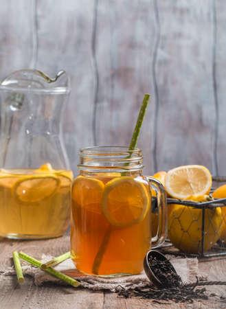 condensation basket: jar of lemon ice tea with straw on wooden background