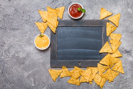nacho: Mexican nacho with sauces and chalk board on gray background, top view, copy space