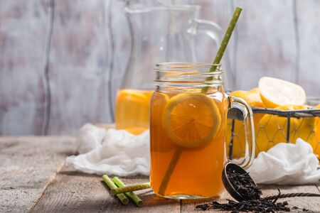 jar of lemon ice tea with straw on wooden background