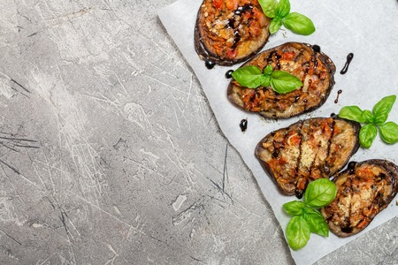copy sapce: Baked eggplant stuffed with vegetables and cheese with addition aromatic herbs and sauce on paper. Delicious vegetarian dish. top view, sopy space