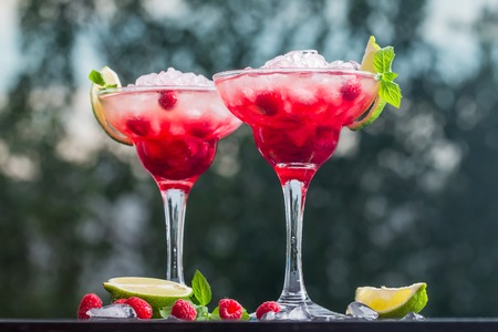 daiquiri alcohol: margarita cocktail with lime and raspberries on nature background