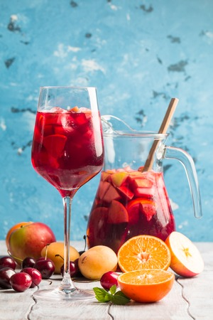 Refreshing sangria or punch with fruits in glass and pincher Stock Photo