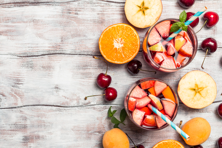Refreshing sangria or punch with fruits in glasses, top view, copy space