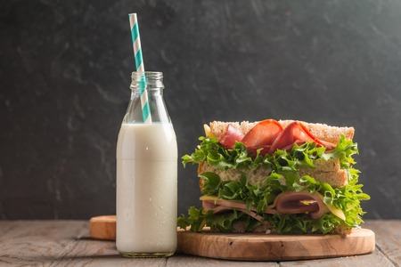 medium group: Club sandwich on a rustic table with milk Stock Photo