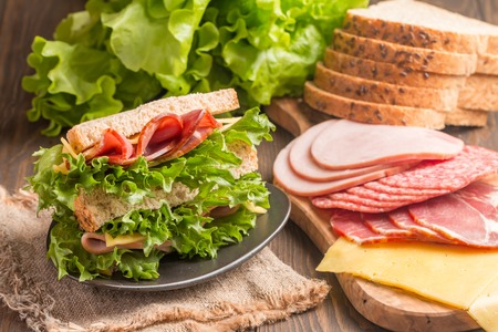 medium group of people: Club sandwich on a rustic table with ingredients