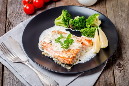 fish sauce: Grilled Salmon Steak with Broccoli, Cream sauce and Lemon Wedges on wooden background