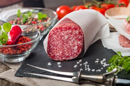 Delicious Salami with cherry tomatoes, spices and olive oil on wooden table