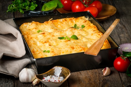 Delicious traditional italian lasagna  with ingredients served on rustic  wooden table Reklamní fotografie - 62996004