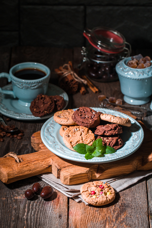sugar cookie: Chocolate chip cookies on plate with coffee on dark wooden table.