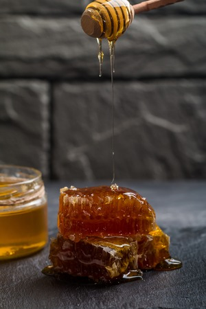 Honey dripping from a wooden honey dipper on the honeycomb on dark background Stock Photo