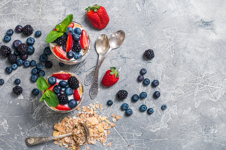 dairy product: Baked granola with  yogurt and berries in glasses, on gray background, top view.