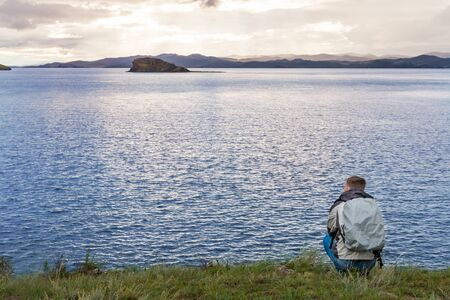squatting: Traveler squatting is enjoying the sunrise over baikal lake