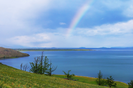 the taiga: Rainbow over calm water of taiga lake, Baikal, Russia Stock Photo