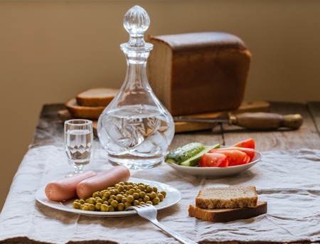 canned peas: Canned green peas and sausage on the white plate with bread and vodka  on linen tablecloth background