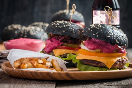 vegetable carbon: Gourmet black burger with berry sauce, french fries and drink on wooden table and dark background Stock Photo