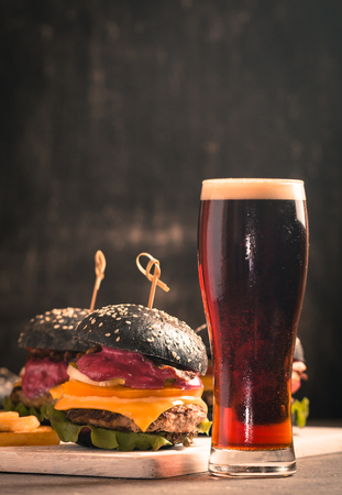 Gourmet black burger with berry sauce, french fries and beer on wooden table and dark background Stock Photo
