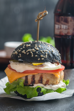 Homemade black burger with grilled chicken patty on dark background Stock Photo