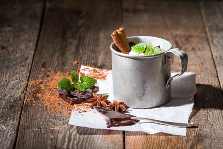 Vintage mug of hot chocolate with cinnamon sticks over dark wooden background. Stock Photo