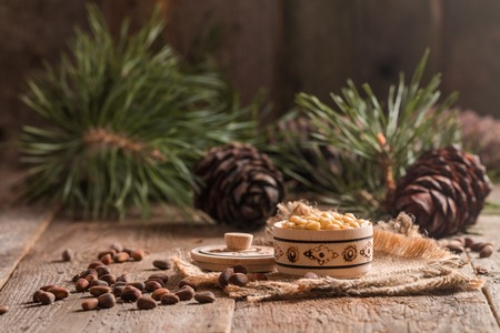 siberian pine: Cedar nuts and branch with cone on wooden background