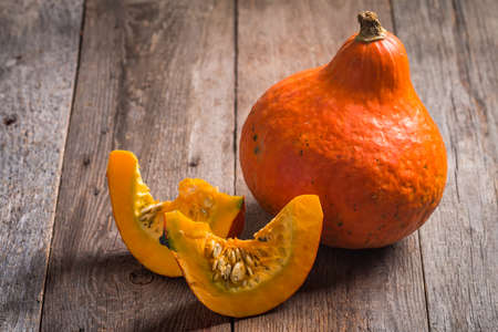 Orange Pumpkins with pieces on wooden background