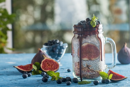 Glass jar of healthy breakfast with muesli, pudding with chia seeds, fresh fig and berries on blue background Stock Photo