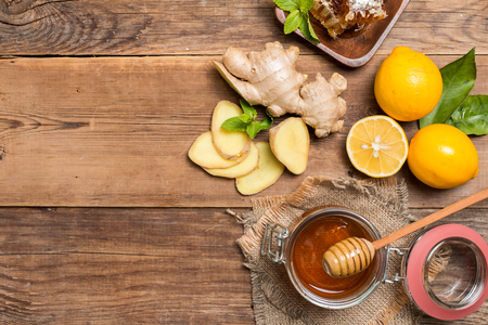 Cup of ginger tea with lemon and honey on wooden background, top view with copy space