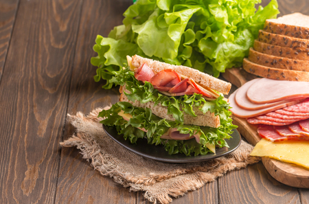 medium group: Club sandwich on a rustic table with ingredients