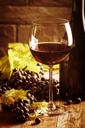 des vins: Red wine and grapes in vintage setting on wooden background