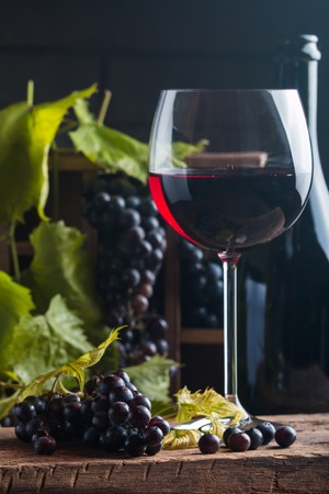 vins: Red wine and grapes in vintage setting on wooden background