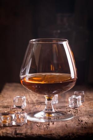 Glass of brandy or cognac on old oak wooden table. Dark photo.