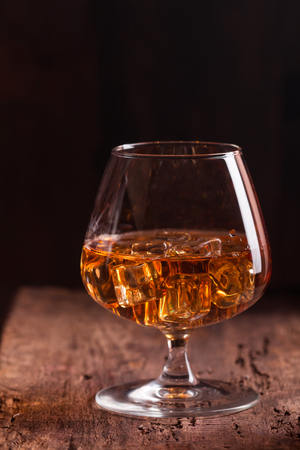 snifter: Glass of brandy or cognac with ice on old oak wooden table. Dark photo.