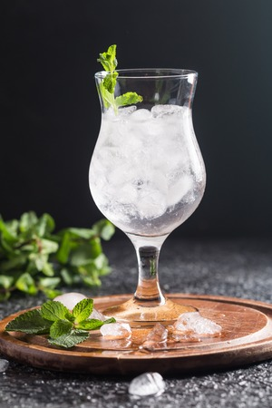 Misted glass of water with ice and mint on black background