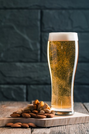unbottled: Glass of light beer with bubbles near black wall