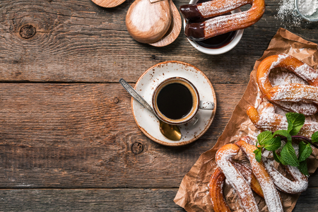 churros, coffee and hot chocolate on wooden table, top view