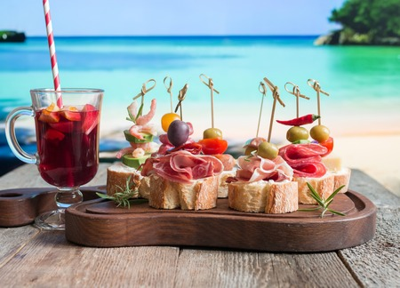 Set of Spanish tapas served on a sliced baguette with sangria on wooden table against the sea Stock Photo