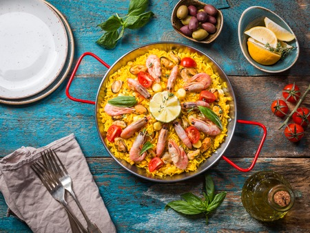 Traditional seafood paella in the fry pan on a wooden old table, top view Reklamní fotografie