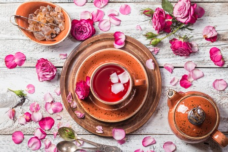 Rose buds tea in a cup, flowers and tea pot on white wooden table, top view.