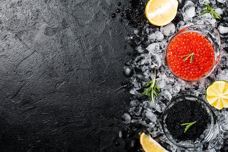 黒の背景上の氷に赤と黒のキャビアとガラスのボウル。健康食品。コピー スペース平面図 写真素材