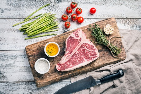 Raw T-bone Steak for grill or BBQ on aged cutting board over white wooden background, top view Stock Photo