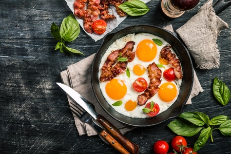 Breakfast set. Pan of fried eggs with bacon and fresh tomato on black background, top view
