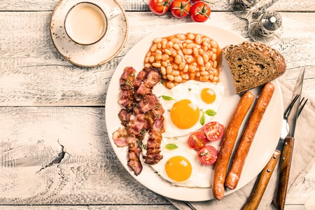 Traditional English Breakfast - sunny-side-up fried eggs, sausages, beans and bacon on white plate with coffee, top view Stock Photo