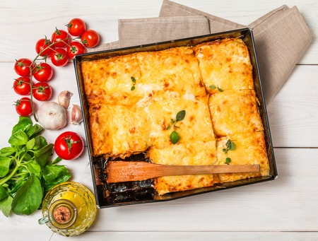 Delicious traditional italian lasagna with ingredients served on white wooden table, top view Standard-Bild