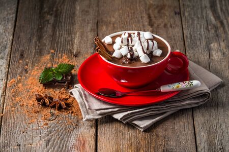 Red cup of hot chocolate with marshmallows on a wooden table